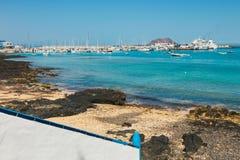 Sikt av den offentliga stranden i Corralejo med porten i bakgrunden Royaltyfria Bilder