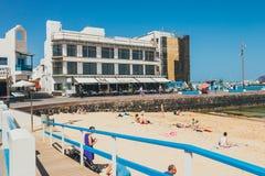 Sikt av den offentliga stranden i Corralejo med porten i bakgrunden Royaltyfri Foto