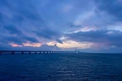 Sikt av den Oresund bron under solnedgång över det baltiska havet royaltyfria foton