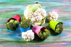 Sikt av den organiska broccoli och blomkålen i kulöra hinkar Begrepp för jordbruksprodukter för säsongsbetonad skördskörd lokalt  arkivbild