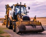 Sikt av den parkerade grävaren med hydraulisk service ner royaltyfri bild