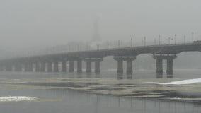 Sikt av den Paton bron i vinter Snöfall i Kiev nära den Dnieper floden stock video
