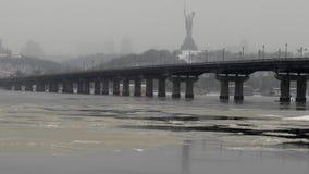 Sikt av den Paton bron i vinter Snöfall i Kiev nära den Dnieper floden Timelapse arkivfilmer