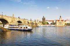 Sikt av den Prague, Charles bron och den Vltava floden med turist- fartyg som svävar förbi på en sommardag, Arkivbild