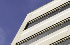 Sikt av den rena affärsbyggnadsfasaden framme av djupblå himmel Arkivfoto