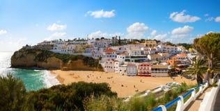 Sikt av den sandiga stranden som omges av typiska vita hus på en solig vårdag, Carvoeiro, Lagoa, Algarve, Portugal royaltyfria bilder