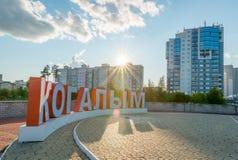 Sikt av den Siberian staden av Kogalym med ett stadstecken på förgrund på solnedgången (Juli, 2015) Royaltyfri Bild