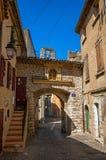Sikt av den stendörren, trappuppgången och klockan i gata på den historiska byn av Rians Arkivfoto