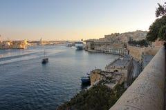 Sikt av den storslagna hamnen i Valletta under solnedgång Tre städer och stora kryssningeyeliner in långt arkivfoto