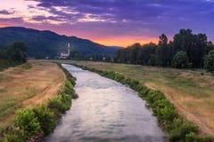 Sikt av den suddiga rörelseNisava floden och den gamla fabriken under livlig färgrik solnedgång Royaltyfria Bilder