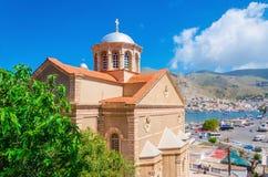 Sikt av den typiska grekiska kyrkan med det röda taket med stadsport i bac Royaltyfri Fotografi