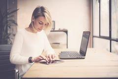Sikt av den unga härliga kvinnan som arbetar på trätabellen Kvinnlign räcker den rörande minnestavlan på arbetsplats Begreppsaffä royaltyfria foton