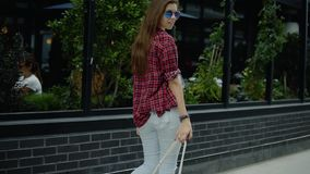 Sikt av den unga kvinnan med den långa hår och ryggsäcken som går nära stadsgatakafét stock video