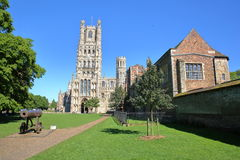 Sikt av den västra framdelen av domkyrkan från en offentlig trädgård med ett vapen i förgrunden i Ely, Cambridgeshire, Norfolk, U royaltyfri foto