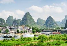 Sikt av den Yangshuo staden, den härliga bron och karstberg royaltyfri foto