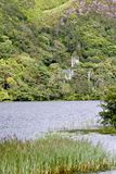 Sikt av dengotiska kyrkan på det Kylemore godset, över sjön som är västra av Irland Arkivfoto