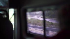 Sikt av det öppna fönstret av bilen som kör på vägen arkivfilmer