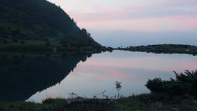 Sikt av det aftonsjön och berget i de Carpathians bergen med rök från branden på kusten av sjön stock video