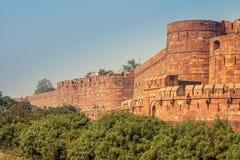 Sikt av det Agra fortet med en blå himmel och gröna buskar på framdelen Det Agra fortet är ett historiskt fort i staden av Agra Arkivfoto