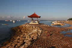 Sikt av det blåa havet, fartyg och stenpir med paviljongen i Bali Arkivfoto
