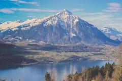 Sikt av det Burgfeldstand berget av emmentalerfjällängar med den klara sjön Fotografering för Bildbyråer