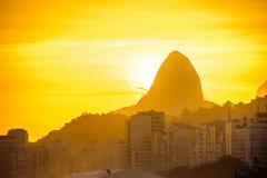 Sikt av det Dois Irmaos berget på bakgrunden av den guld- solnedgången fr royaltyfri foto