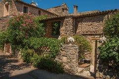 Sikt av det gamla stenhuset med stenstaketet och blommor på den Les Arcs-sur-Argens Royaltyfri Fotografi