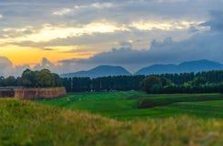 Sikt av det gröna fältet för gräs, träd och Tuscany kullar och berg royaltyfria bilder