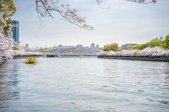 Sikt av det gula turist- fartyget i floden och bron från Arkivfoto