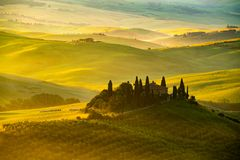 Sikt av det härliga bergiga Tuscan fältet i det guld- morgonljuset arkivfoto