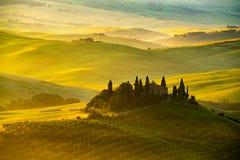 Sikt av det härliga bergiga Tuscan fältet i det guld- morgonljuset arkivbilder