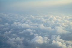 Sikt av det härliga drömlika fluffiga abstrakta vita molnet med blå himmel och ljus bakgrund för soluppgång från flygplanfönster arkivbild