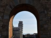 Sikt av det lutande tornet av Pisa till och med båge arkivfoto