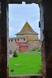 Sikt av det monarkiska tornet från den förstörda templet i fästningen Oreshek nära Shlisselburg, Ryssland Arkivfoto