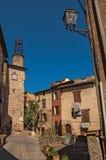 Sikt av det stenhus och tornet i en gata under blå himmel på den Les Arcs-sur-Argens Arkivfoton