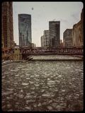 Sikt av djupfrysta Chicago River och det högstämda spåret under tungt snöfall royaltyfri bild