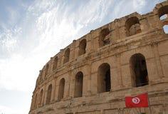 Sikt av El Jem och flaggan av Tunisien Arkivbild