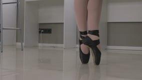 Sikt av en ballerina som står en-pointe på spetsarna av hennes tår i ett par av balettskor lager videofilmer