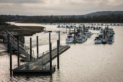 Sikt av en brygga och en pir som leder till en flottilj av förtöjde yachter på floden Medway i Rochester, England, UK arkivfoto