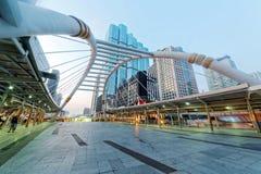 Sikt av en fot- planskild korsning i centrum av den Bangkok staden med höga löneförhöjningbyggnader i bakgrunden i ottaljus Arkivfoton