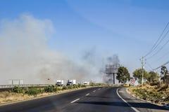Sikt av en huvudväg observera en brand med svart rök och bilar som cirkulerar royaltyfri bild