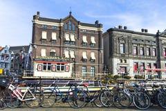 Sikt av en kanal och cyklar i Amsterdam arkivfoto