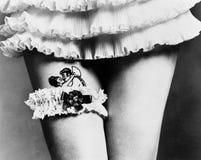 Sikt av en kvinna som döljer en tatuering med en strumpeband på hennes lår (alla visade personer inte är längre uppehälle, och in Arkivbilder