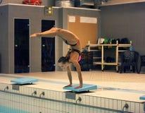 Sikt av en kvinnlig dykaredykning in i pölen stå på armar med ben upp Fotografering för Bildbyråer