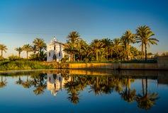 Sikt av en kyrka med en reflexion i vattnet och en bro över floden i den Alboraya regionen spain valencia royaltyfria foton