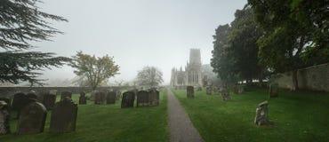 Sikt av en kyrka till och med en kyrkogård på en dimmig morgon, England Royaltyfri Bild