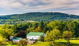 Sikt av en lantgård och de Piegon kullarna, nära vårdunge, Pennsylv royaltyfri bild