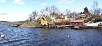 Sikt av en liten hamn för små fartyg i Vaxholm var många hus har deras egna skeppsdockor Arkivbild
