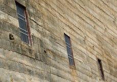 Sikt av en mycket lantlig vägg med gallerförsedda fönster arkivbild