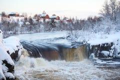 Sikt av en plan vattenfall med byn på kullen Solnedgång på vintersäsongen Område av byn Nadvoitsy, Segezha, Karelia, royaltyfri foto